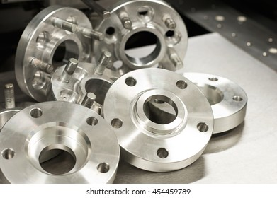 Kit of new metal mold of wheel spacers and bolts. CNC milling and lathe industry. Metal engineering. Indoors closeup horizontal  image.