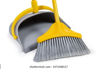 Kit of the yellow plastic broom with gray bristles for sweeping floors and dustpan on a white background, working parts close-up