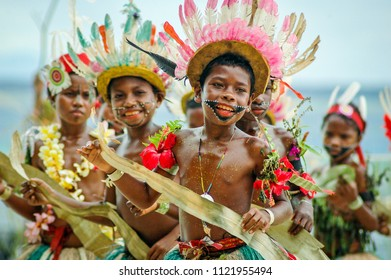 Kitava, Trobriand Is./ Papua New Guinea - October 28 2010: Boys  wearing costumes made from local materials perform a welcome dance for visitors from a small cruise ship
