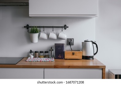 Kitchen accessories like kettle, coffee pot, cups, napkin, tea, coffee and condiments