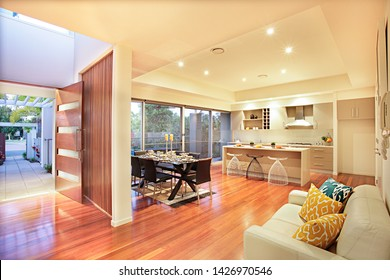 Kitchen with appliances, wooden floor, expensive furnitures can see in this room, door and shiny floor have made with wood, pillows with designs on the sofa, green trees, grand front entrance.