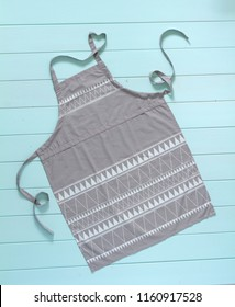 kitchen apron of gray color in full mesh on a white background. the loop on the apron is folded in the form of the heart, the love of cooking