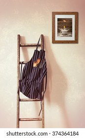 Kitchen apron hanging on the rung of a rustic wooden ladder with spoons and whisk
