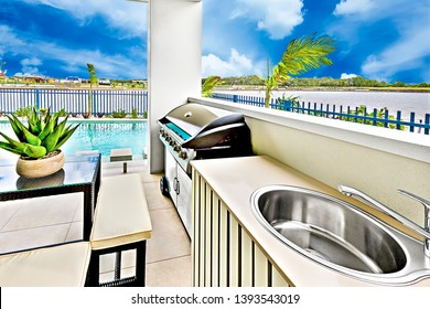Kitchen area near outdoor swimming pool, green plant pot on the glass table, trees arround the garden, river side with beautiful forests.