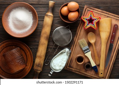 Kitchen background. Flour, sour cream, eggs and wooden utensils on the kitchen table.