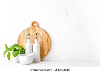 Kitchen background, front view of utensils standing on white countertop, contemporary kitchen space concept, blank space for a text