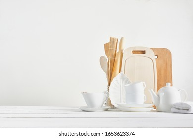 Kitchen background for mockup with spoon, teapot, cups, rolling pin, bowls on wooden table on white background. Blank space for home kitchen concept.