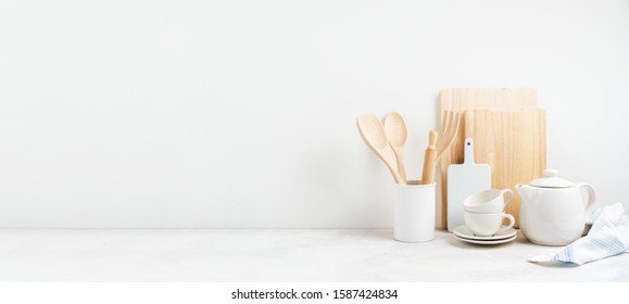 Kitchen background for mockup with teapot, cups,  rolling pin, bowls for cooking and baking utensils on the table on white background. Blank space for a text, home kitchen decor concept. Wide banner.