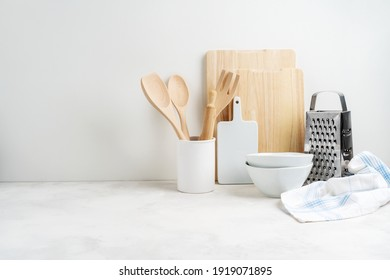 Kitchen background mockup with teepot and cooking, baking utensils rolling pin, cutboard, bowls on the table on white background. Blank space for a text, home kitchen decor concept.