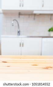 Kitchen background table in foreground kitchen countertop and sink blurred in the background