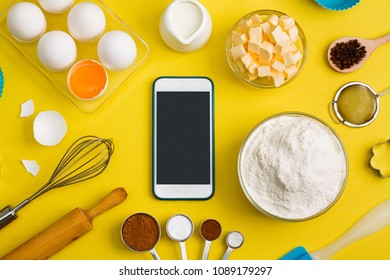 Kitchen baking mobile phone application service website mockup with eggs, butter, milk, floor, spices tools whisk, brush, rolling pin, sieve, whisk, bake ware shape cookie cutter on yellow
