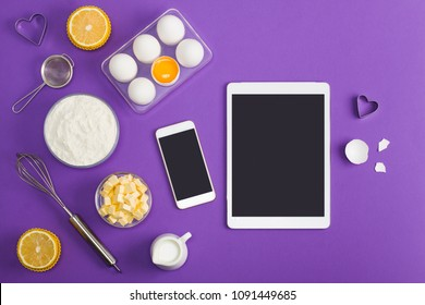Kitchen baking mobile phone tablet application service website mockup with eggshells, butter, milk, floor, lemon muffin, tools sieve, whisk bake ware heart shape cookie cutter on violet background