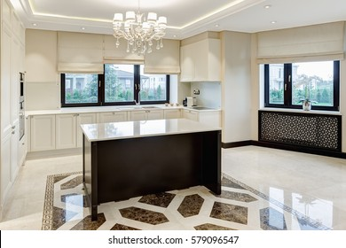 Kitchen bar of the center of room and crystal chandelier over. Big windows with beige jalousie with beautiful view on garden. Dining room in beige, white and black colors.