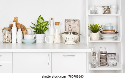 Kitchen bench and shelf with various utensils on white background