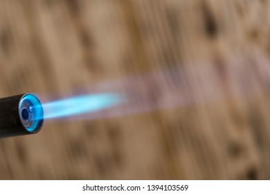 kitchen blowtorch gas blue flame, wooden background