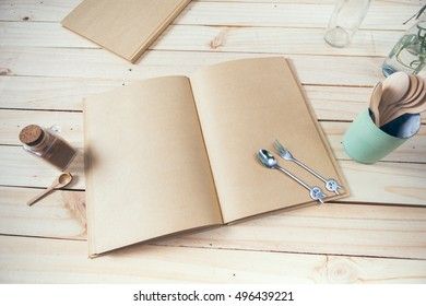 Kitchen book with blank pages to write text on the wooden background with spoons. Copy space. Food background - Shutterstock ID 496439221