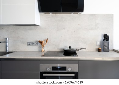 Kitchen with built in appliance, electric cooker hood, stove, oven and sink. Frying pan on glass ceramic surface at marble countertop close to wooden spoons and knives, under white cupboards