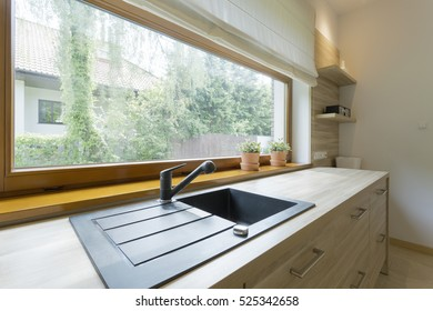 Kitchen cabinet with a black stone sink by a large horizontal window