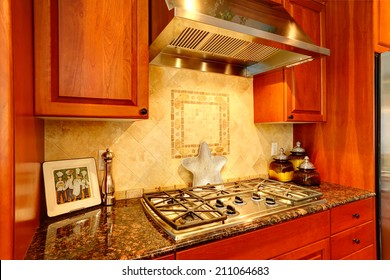Kitchen cabinet with granite top and built-in stove. View of tile back splash trim