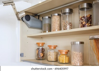 Kitchen cabinet with opened fronts with kitchen bench shelves with various food ingredients on white background
