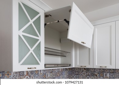 Kitchen cabinet with opened fronts with dish holder shelves inside. Lift system for bi-fold fronts for direct access in kitchen cabinets. Kitchen in a neoclassical style with wooden white fronts.