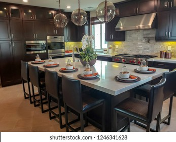 Kitchen Cabinets in Upscale Home Setting.  Dark wood style, modern with appliances and island