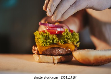 Kitchen chef assembling cheeseburger by adding onion with gloves on