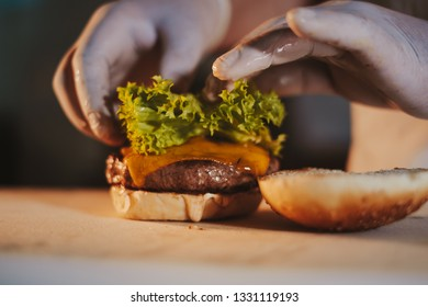 Kitchen chef assembling cheeseburger by adding salad with gloves on