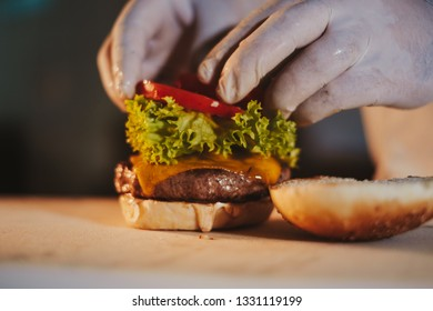 Kitchen chef assembling cheeseburger by adding tomato with gloves on