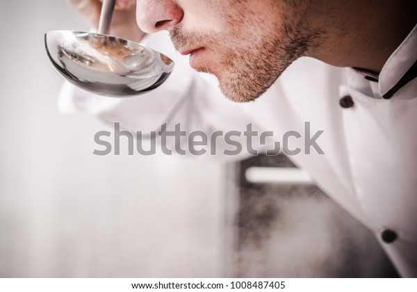 Kitchen Chef Smelling Soup in Professional Grade Metal Ladle To Make Sure Everything is Cooking Well.