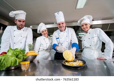 Kitchen chef with young apprentices, teaching to make decorative fruit basket