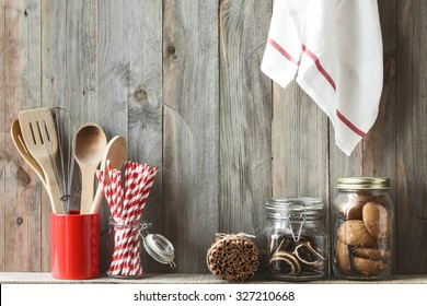 Kitchen cooking utensils in ceramic storage pot and cookies on a shelf on a rustic wooden wall