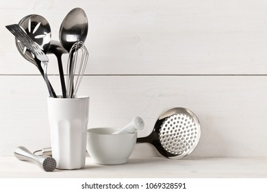 Kitchen cooking utensils in white cup with pestle and mortar on white table with white wooden board background