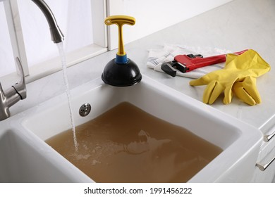 Kitchen counter with clogged sink, plunger and plumber's accessories