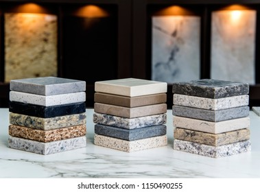 Kitchen counter top color samples made of natural granite, marble and quartz stone inside the countertop store on the white carrara marble slab