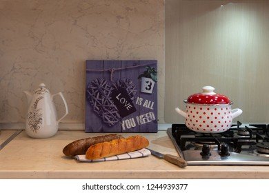 Kitchen counter top with tea pot, bread, stewpot on a stove