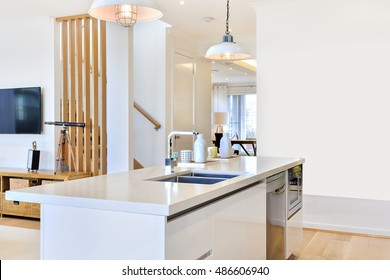 Kitchen counter top with the view of inside house with hanging lamps with white walls through the wooden pillars