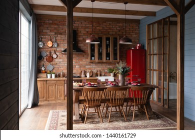 Kitchen in a country house. Wooden kitchen set with big table and chairs standing near the panoramic window to the floor, red refrigerator, blue wooden wall, pans hanging on a brick wall. Loft style.