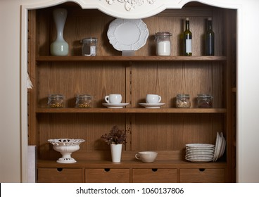Kitchen cupboard with nice rustic dinnerware. Wooden kitchen cabinet cupboard with many white dishes, plates, cups, jars and wine bottles on shelves