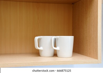 Kitchen cupboard with white cups