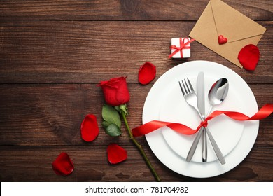 Kitchen cutlery on white plate with envelope and red rose