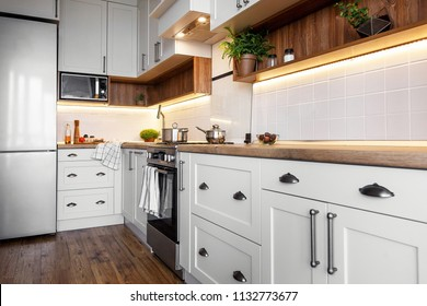 kitchen design in scandinavian style. Stylish kitchen interior with modern cabinets and stainless steel appliances. cooking food. green plants decor, wooden worktop, sink and stove