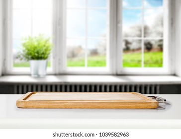 Kitchen desk of free space for your decoration on white desk and blurred background of window. One green plant on window sill. Spring time.