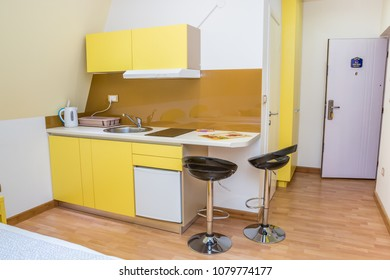 "Kitchen or dining area of studio apartment. Modern three stars hotel room interior with open door. Letter on Serbian language ""APARTMAN"" means APARTMENT."