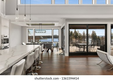 Kitchen, Dining, and Living Room in Amazing Contemporary Style Luxury Home. Large Windows Reveal Sweeping Water Views and Outdoor Covered Patio and Deck.