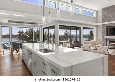 Kitchen, Dining, and Living Room in New Contemporary Luxury Home. Features Stunning Views. Large Waterfall Island in Kitchen Overlooks Open Concept Dining and Living Room.