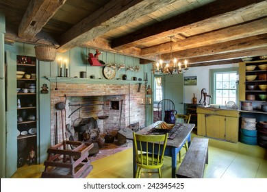 The kitchen, dining room and fireplace in a 17th century primitive colonial style home.  This home dates to before the American revolutionary war, and contains antiques from the late 18th century.
