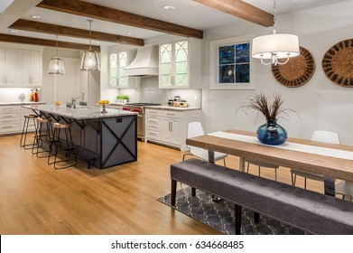 Kitchen and Dining Room in New Luxury Home with Large Island, Hardwood Floors, Range Hood, and Glass Fronted Cabinets, Horizontal Orientation