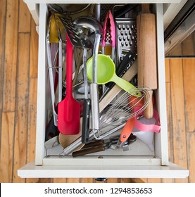 a kitchen drawer packed with utensils is shown