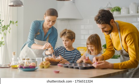 In the Kitchen: Family of Four Cooking Muffins Together. Mother and Daughter Mixing Flour and Water to Create Dough for Cupcakes, Father, Son Preparing Paper Lines for Pans. Children Helping Parents